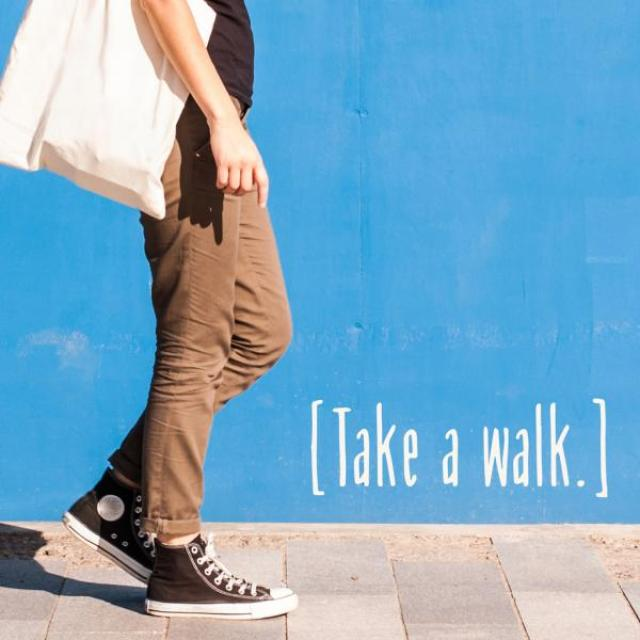 "Person in sneakers with a bag walking on a sidewalk against a cheerful blue wall. Text: ""Take a walk"""