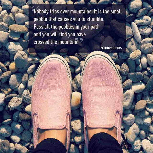 "Photo of pink shoes on pebbles with text saying ""Nobody trips over mountains. It is the small pebble that causes you to stumble. Pass all the pebbles in your path  and you will find you have crossed the mountain."""