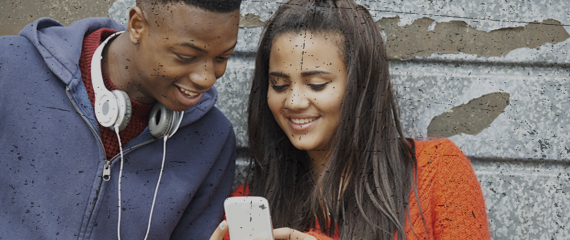 teenage boy with headphones around neck and teenage girl holding phone. both are looking at the phone and smiling
