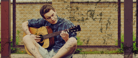 Young man sitting with legs crossed and playing guitar outside