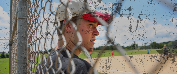 Teenage boy in baseball cap standing in front of fence facing a baseball field